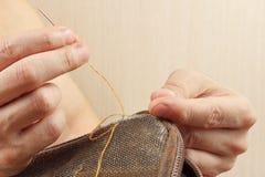 Mãos do saco durável de pano do reparo do esgoto com fim da agulha acima foto de stock royalty free
