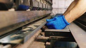 Mãos do trabalhador com um workpiece do metal Fornece uma peça a uma máquina de dobra vídeos de arquivo