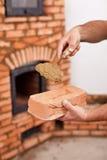 Mãos do trabalhador da alvenaria com o almofariz do tijolo e da argila na pá de pedreiro Fotos de Stock Royalty Free
