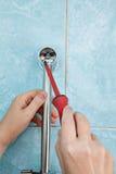 Mãos do trabalhador do close-up fixadas para murar o chuveiro do suporte, usando o screwdr Foto de Stock