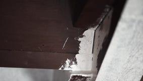 Mãos do trabalhador do homem que pintam profissionalmente paredes cinzentas no branco com escova grande filme