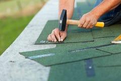 Mãos do trabalhador que instalam telhas do telhado do betume Foto de Stock