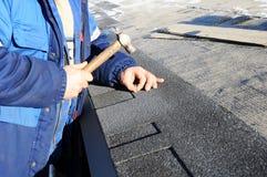 Mãos do trabalhador que instalam telhas do telhado do betume Martelo do trabalhador nos pregos no telhado Foto de Stock Royalty Free