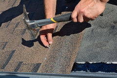 Mãos do trabalhador que instalam telhas do telhado do betume Martelo do trabalhador nos pregos no telhado O Roofer está marteland Imagens de Stock