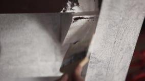 Mãos do trabalhador que pintam profissionalmente paredes cinzentas no branco com escova grande filme