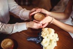 Mãos dos amantes novos que guardam um café quente do copo Foto de Stock Royalty Free