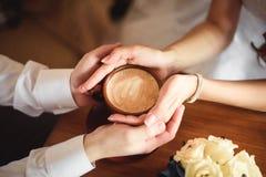 Mãos dos amantes novos que guardam um café quente do copo Foto de Stock