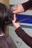 Mãos dos barbeiros que cuting o cabelo preto Imagem de Stock