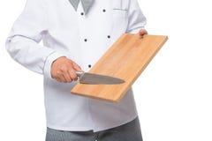 Mãos dos cozinheiros chefe com placa de corte e uma faca afiada Fotos de Stock