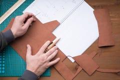 Mãos dos curtidores no trabalho com furador, capa impermeável e couro Foco selecionado, fim acima foto de stock