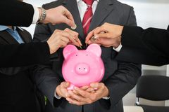 Mãos dos empresários com moedas e piggybank Foto de Stock