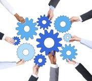 Mãos dos executivos que guardam símbolos da engrenagem Imagem de Stock