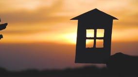 Mãos dos homens e das mulheres que mantêm um modelo da casa e as chaves contra o por do sol Silhueta de uma casa de papel video estoque
