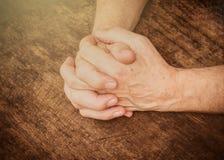Mãos dos homens que rezam no livro de madeira aberto Imagens de Stock
