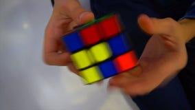 Mãos dos meninos que resolvem o cubo do rubik video estoque