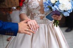 Mãos dos noivos com alianças de casamento em flores Foto de Stock
