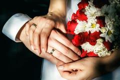 Mãos dos noivos com alianças de casamento, ramalhete do casamento Foto de Stock Royalty Free