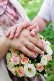 Mãos dos noivos com anéis no ramalhete do casamento Foto de Stock Royalty Free