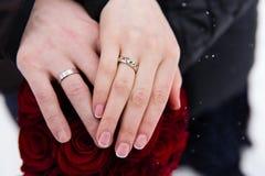 Mãos dos noivos com anéis no ramalhete do casamento Foto de Stock