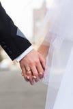 Mãos dos noivos com uma aliança de casamento Fotos de Stock