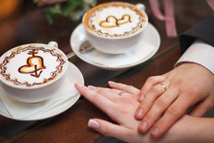 Mãos dos noivos na tabela, copos de café do latte Imagem de Stock Royalty Free