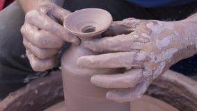 Mãos dos oleiro cobertas na argila que forma um potenciômetro em um fim da roda acima imagens de stock royalty free