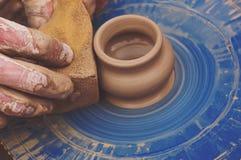 Mãos dos oleiro que dão forma a uma bacia fora da argila fotografia de stock
