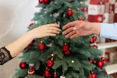 Mãos dos pares com fundo da árvore de Natal Foto de Stock
