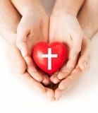 Mãos dos pares que guardam o coração com símbolo transversal imagem de stock