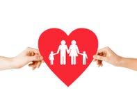 Mãos dos pares que guardam o coração vermelho com família Imagens de Stock