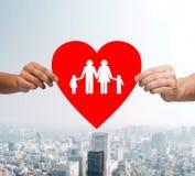 Mãos dos pares que guardam o coração vermelho com família Fotografia de Stock