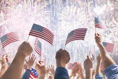 Mãos dos povos que guardam as bandeiras dos EUA imagens de stock royalty free