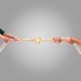Mãos dos povos que puxam a corda em um fundo cinzento Conceito da cooperação Foto de Stock