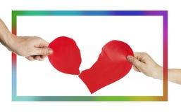 Mãos dos povos que rasgam o coração distante em um quadro multi-colorido Conceito do dia do ` s do Valentim Coração rasgado no fu foto de stock