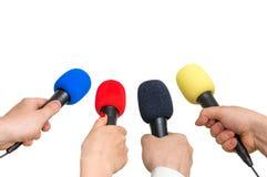 Mãos dos repórteres com muitos microfones Imagem de Stock