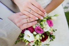 Mãos e anéis no ramalhete do casamento Imagens de Stock