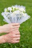 Mãos e anéis no ramalhete do casamento Fotografia de Stock