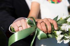 Mãos e anéis no ramalhete do casamento Fotografia de Stock Royalty Free