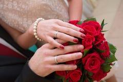 Mãos e anéis no ramalhete do casamento Fotos de Stock Royalty Free