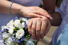 Mãos e anéis no ramalhete do casamento Foto de Stock