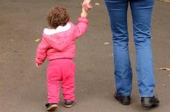Mãos e caminhadas da posse da criança no parque com sua mãe Fotos de Stock Royalty Free