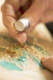 Mãos e dedal que fazem o bordado com linha do ouro Fotografia de Stock Royalty Free