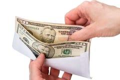 Mãos e envelope com dólares Fotos de Stock