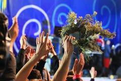 Mãos e grinaldas de ondulação dos povos em um concerto Fotos de Stock Royalty Free