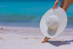 Mãos e pés fêmeas com o chapéu branco na praia fotografia de stock royalty free