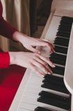 Mãos e piano Parte do corpo mãos nas chaves brancas do piano que joga uma melodia As mãos das mulheres no teclado de Foto de Stock Royalty Free