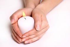 Mãos e vela branca Fotografia de Stock