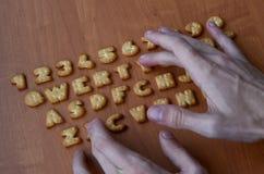 Mãos em botões do teclado do biscoito Fotografia de Stock Royalty Free