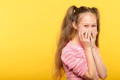 Mãos embaraçados de sorriso tímidas da boca da coberta da menina fotografia de stock