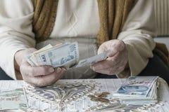 Mãos enrugadas que contam cédulas da lira turca Fotografia de Stock